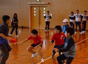 佐賀大生とともにフラッグフットボールを楽しむ子どもたち=佐賀市の久保泉小体育館