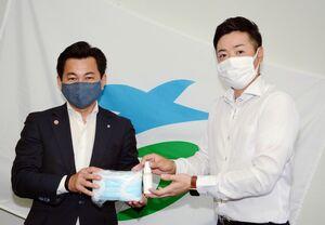 松尾佳昭町長に光触媒のスプレーとセットのマスクを手渡す前田晶平社長(右)=有田町役場