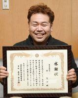 感謝状を手にし、笑顔を見せる平寛士さん=神埼市の神埼署