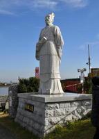 昇開橋をバックに立つ徐福像は、友好の証しとして慈渓市から贈られてきた=佐賀市諸富町