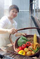 野菜を蒸し窯に入れる井上さん=長崎県雲仙市小浜町