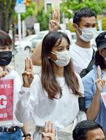 仲間と一緒に3本指を掲げ、ミャンマー国軍への抗議の意思を示すポザーコさん(中央)=18日、佐賀市の駅前まちかど広場