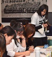 参加者たちが「どんな時に幸せを感じるか」を考えるのを眺める竹下真由さん(右奥)=佐賀市のさがレトロ館