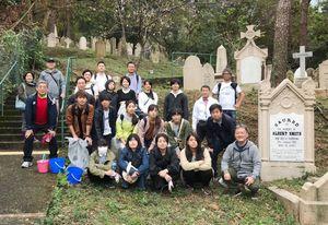 県出身者の墓地を清掃した香港佐賀県人会のメンバーと佐賀大学の学生ら=香港の国際墓地