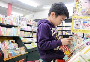 営業継続が決まった店内で本を読みふける小学生=有田町の積文館書店有田店