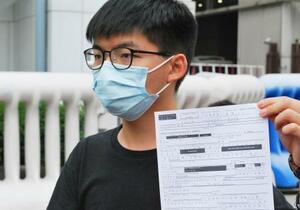 24日、香港中心部の警察署の外で記者会見し、保釈関連の文書を見せる民主活動家、黄之鋒氏(共同)