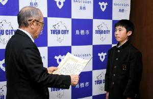 久光理・鳥栖市選挙管理委員長から全国表彰の伝達を受ける隈本裕亮さん(右)=鳥栖市役所