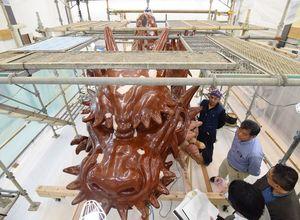 足場が組まれ、総修復と塗り替えが進む7番曳山「飛龍」=唐津市北城内の修理庫「曳山の蔵」