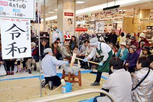 新元号発表を祝った餅つき大会で、きねを振るうスタッフら=唐津市のまいづる本店ショッピングプラザ