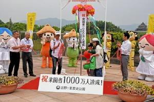 1000万人目の来場者となりくす玉を割った稲田雅三さん(左から3人目)と家族ら=吉野ケ里歴史公園