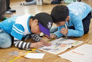 気持ちを込めて風船に付ける手紙を書く子どもたち=佐賀市若宮の若楠小学校