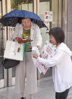 支援を呼び掛けるスタッフ(右)と募金をする通行人=佐賀市の玉屋前交差点