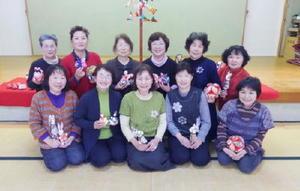 作品を手に、指導者の山﨑マチ子さん(前列中央)を囲む皆さん