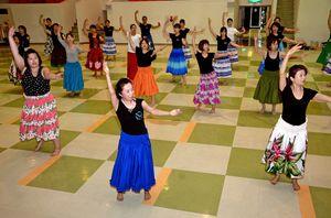 「エ フラ カーコウ! 嬉野」の振り付けを練習する嬉野市内のフラダンス教室メンバー=嬉野市公会堂