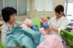 分娩介助の演習体験をした参加者=佐賀市の県立総合看護学院