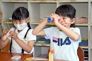 万華鏡が完成し、うれしそうにのぞき込む子ども=唐津市の伊岐佐小