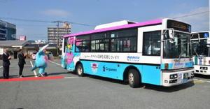 刷新されたサガン鳥栖のラッピングバスを見送る関係者たち=西鉄バス佐賀鳥栖支社