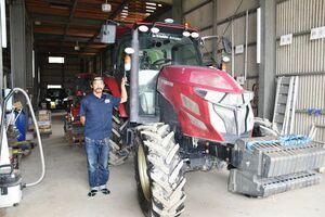 自動操舵装置のついた大型トラクターを手にする古賀洋一郎取締役=神埼市、アグリベースにいやま