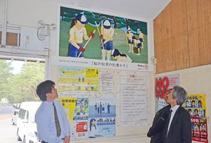 鏡中美術部員が描いたパネル画を見上げる都市右太雄・唐津東RC会長(右)ら=17日