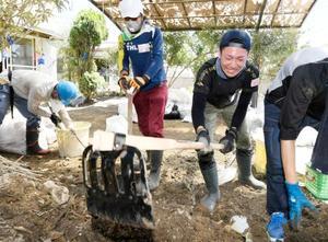 流れ込んだ土を撤去するボランティア=23日午前、岡山県倉敷市真備町地区