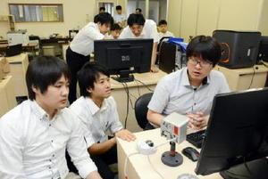 インターンシップの一環で、破砕機プラントのプログラミングを行う電気通信大の学生ら=武雄市の中山鉄工所