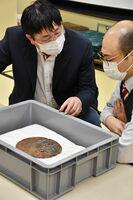ダンワラ古墳から出土したと伝わる鉄鏡を確認する潘偉斌氏(左)=福岡県太宰府市の九州国立博物館