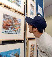 ゴジラの原画に見入る池田学さん=佐賀市の県立美術館