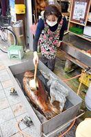 アラに煮汁を掛ける亀山鮮魚店の亀山弘美さん=唐津市中町