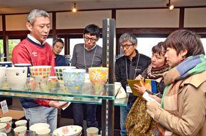 肥前吉田焼の窯元関係者から製品の特徴などを聞くデザインスクールの参加者=肥前吉田焼窯元会館