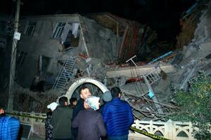 地震で損壊した建物を見る人たち=24日、トルコ東部エラジグ(AP=共同)