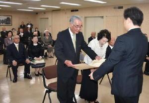 逢阪本部長から勲記を手渡される受章者=佐賀市の県警本部