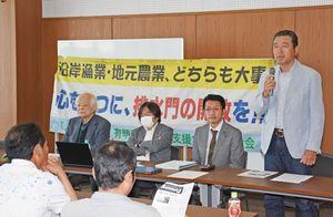 集会で、干拓地の農業の状況を説明する松尾公春さん(右)=佐賀市中の小路の佐賀県弁護士会館