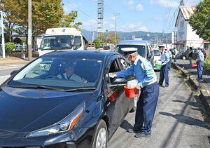 ドライバーにチラシなどを配布する参加者=上峰町の県道坊所城島線