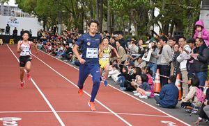 家族連れなどが見つめる中、小学生と競走する藤光謙司選手=佐賀市城内の本丸通り
