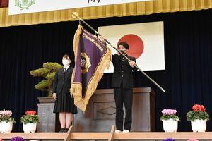伊万里農林高の校旗が3年生の山口武留さん(右)から伊万里実高2年の松尾瑠奈さんに引き継がれた=伊万里市の伊万里農林高
