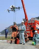 民間業者がドローンを飛ばし、対岸にリードロープを運ぶ訓練に取り組んだ=鹿島市の中木庭ダム周辺