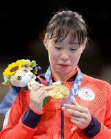 女子フェザー級で優勝し、表彰式で金メダルを見つめる入江聖奈=両国国技館