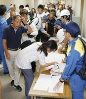 兵庫県宝塚市役所に避難し、受付に並ぶ福井県高浜町の住民=27日午後