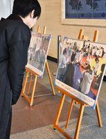 スポーツ交流をする様子を写した写真を眺める来館者=佐賀市の県庁