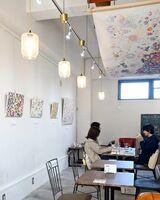 お茶をしながら楓子さんの作品を楽しめるほか、天井には来場者とのコラボ作品を飾る=佐賀市のArukカフェ