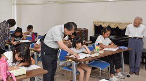講師から助言を受け、夏休みの宿題を進める子どもたち=神埼市中央公民館