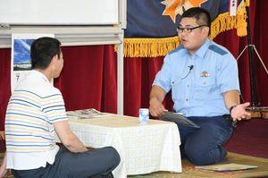 巡回連絡のシミュレーションで地域住民の家を訪れ、防犯情報などを伝える若手警察官=佐賀市の県警察学校