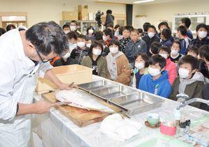 山下淳也さんの包丁さばきを見入る児童ら=小城市芦刈町の芦刈観瀾校