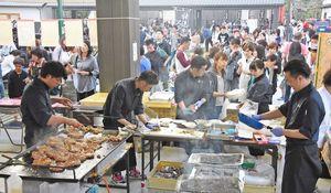 長蛇の列ができて次々と注文が入り、懸命に肉を焼くなど作業をするスタッフたち=神埼市神埼町の長崎街道門前広場