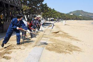 遊歩道(左側)に堆積した砂を砂浜に戻す参加者。昨秋まで砂浜の高さは堤防(中央)より1メートルほど低かった=唐津市の西の浜