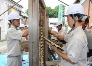 粗壁塗りを体験する塩田工業高建築科の2年生=嬉野市の重要伝統的建造物群保存地区「塩田津」