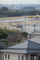 住宅地の奥に見える駐機場を離陸したUH-1Jヘリコプター=神埼郡吉野ヶ里町の陸上自衛隊目達原駐屯地