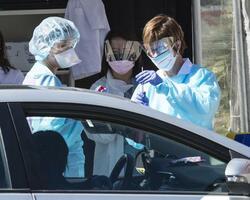 米サンフランシスコの医療施設で、ドライブスルーで新型コロナウイルスの検査を行う人々=3月(UPI=共同)