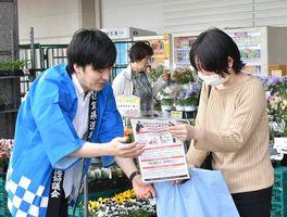 買い物客に啓発グッズを手渡して投票を呼び掛けた街頭活動=佐賀市のゆめタウン佐賀
