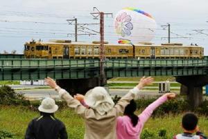 唐津に向けて走る観光列車「或る列車」。沿線の人たちが手を振り、バルーンも歓迎した=23日午前、佐賀市久保田町